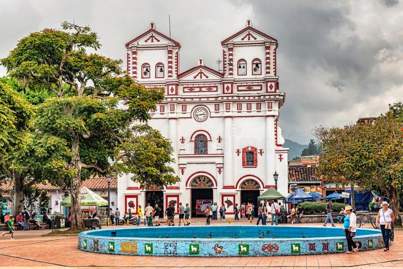 Catholic church. Guatape, Colombia - March 27, 2018: People in front of Colorful Catholic church `Our Lady of Carmen` on the square in village of Guatape near stock images