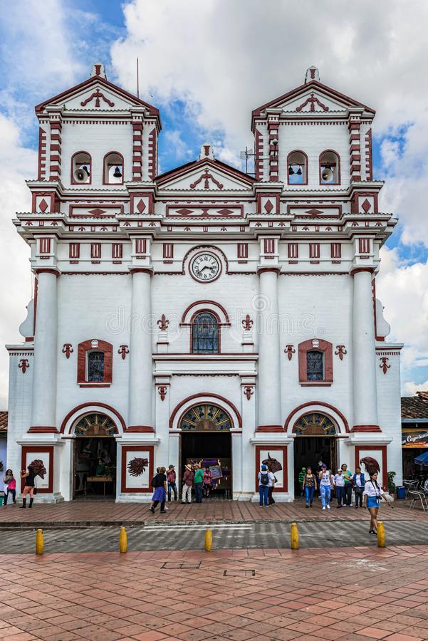 Catholic church. Guatape, Colombia - March 27, 2018: People in front of Colorful Catholic church `Our Lady of Carmen` on the square in village of Guatape near royalty free stock photography
