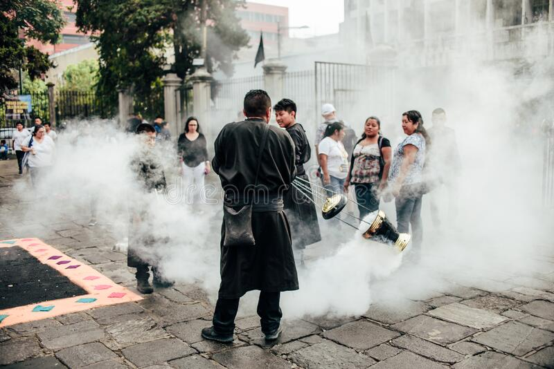 GUATEMALA - April 19: men with black robe spreading scented smoke on the street during easter,  April 19, 2019 in Guatemala City,. Men with black robe spreading royalty free stock photo