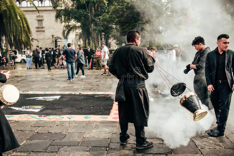 GUATEMALA - April 19: men with black robe spreading scented smoke on the street during easter,  April 19, 2019 in Guatemala City,. Men with black robe spreading stock photos
