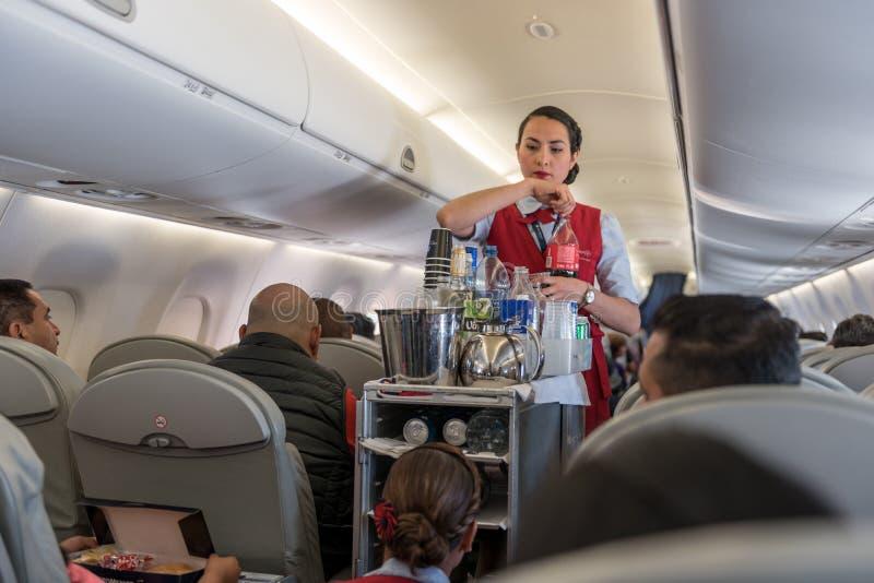 GUATEMALA - 22 DE NOVIEMBRE DE 2017: Aeroplano de AeroMexico, funcionamiento del equipo de la cabina y comida de Provinding imagenes de archivo