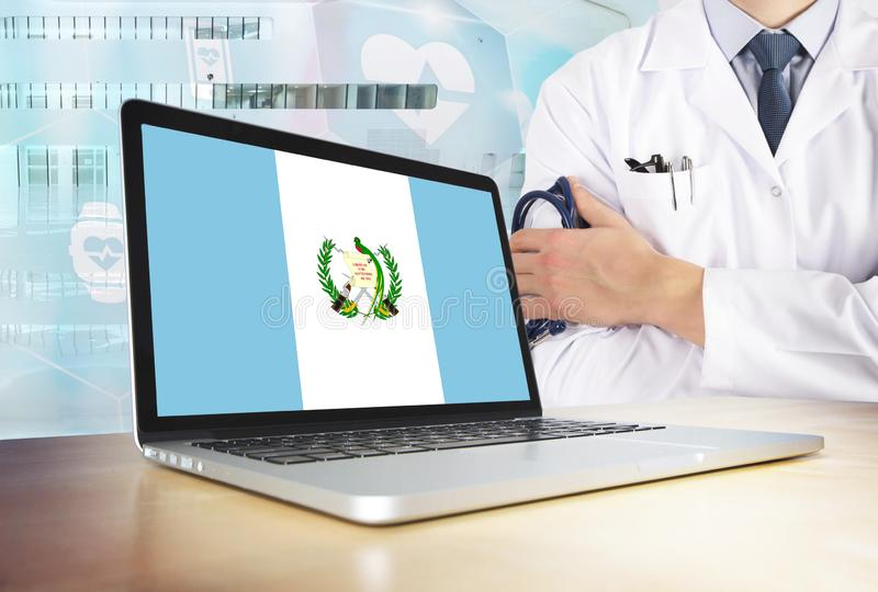 Guatemala healthcare system in tech theme. Guatemalan flag on computer screen. Doctor standing with stethoscope in hospital. Cryptocurrency and Blockchain stock photos