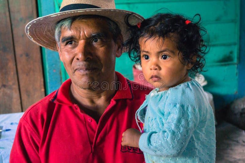 Guatemalaanse koffielandbouwer met kleindochter royalty-vrije stock fotografie