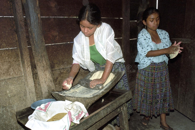 Guatemalan Indian teens preparing tortillas. Guatemala, department Alto Verapaz: group portrait of Indian teenagers and mothers working together, preparing a royalty free stock photo