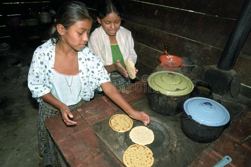 Guatemalan Indian teens preparing tortillas. Guatemala, department Alto Verapaz: group portrait of Indian teenagers working together, preparing a meal, cooking royalty free stock photos