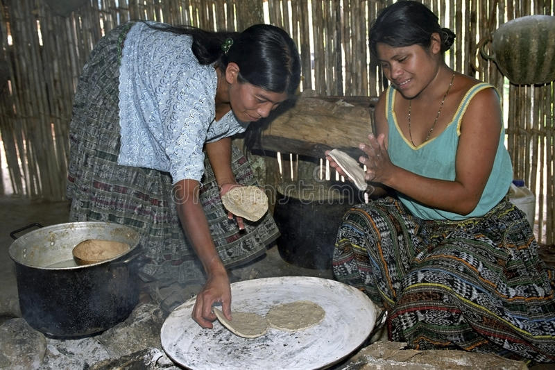 Guatemalan Indian women preparing tortillas. Guatemala, group portrait of Indian women, mother and daughter, of the Angelina Iqui tribe, working together royalty free stock photos
