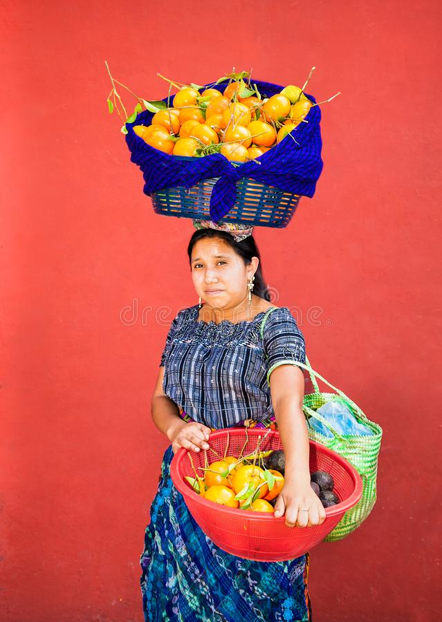Guatemalan woman carries fruit in a baskets at her head and hand stock image
