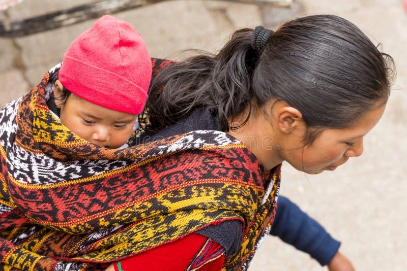 Guatemalanen behandla som ett barn i traditionell rem arkivfoton
