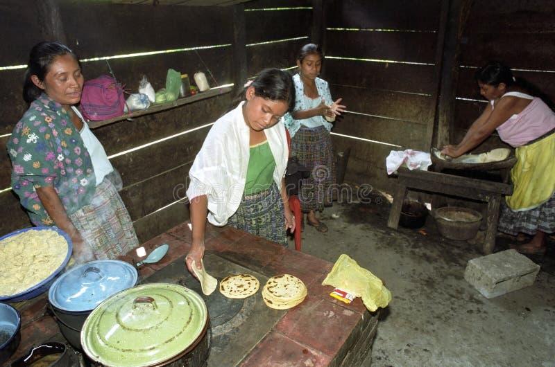 Guatemalansk indisk familj som förbereder tortillor royaltyfria bilder