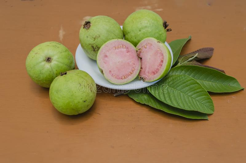 Guava Cross Sections, and Whole Fruits On Leaves stock illustration