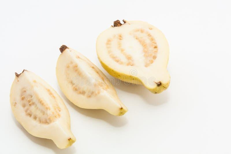 Guava fruit cut into three pieces. Riped guava fruit cut into three pieces arranged in a row stock photo