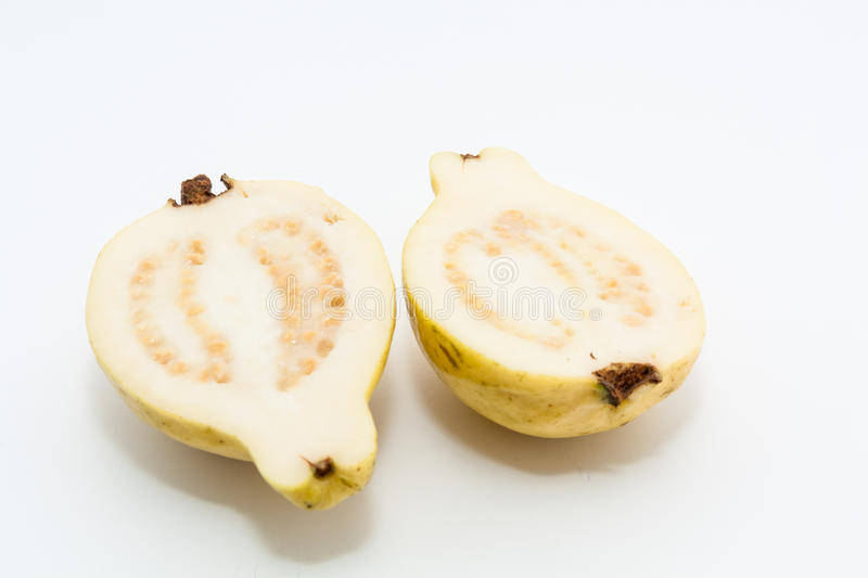 Guava fruit cut into two pieces. On white background royalty free stock images