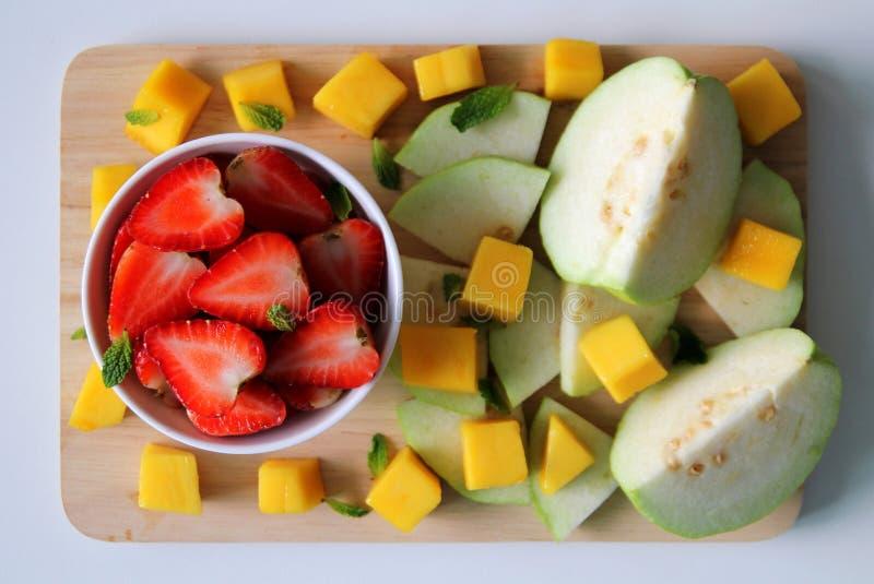 Guave, mango en aardbei met bladeren van munt op de witte achtergrond stock afbeeldingen