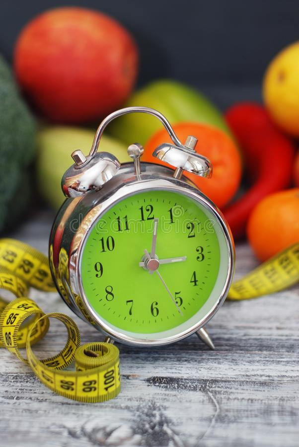 gubi czas target2057_0_ Owoc, warzywo i budzik na pojęciu, stole diety i sprawności fizycznej, zdjęcia royalty free
