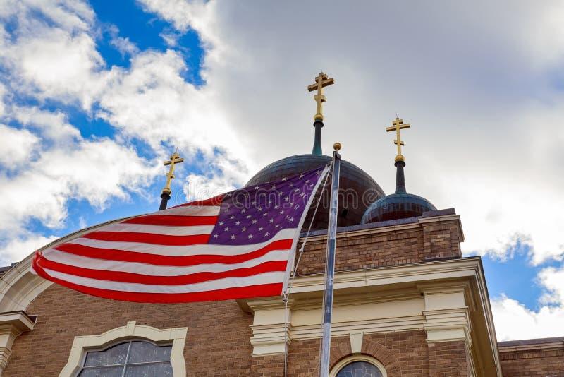Guden välsignar den Amerika amerikanska flaggan och kyrkakyrktorn arkivbild