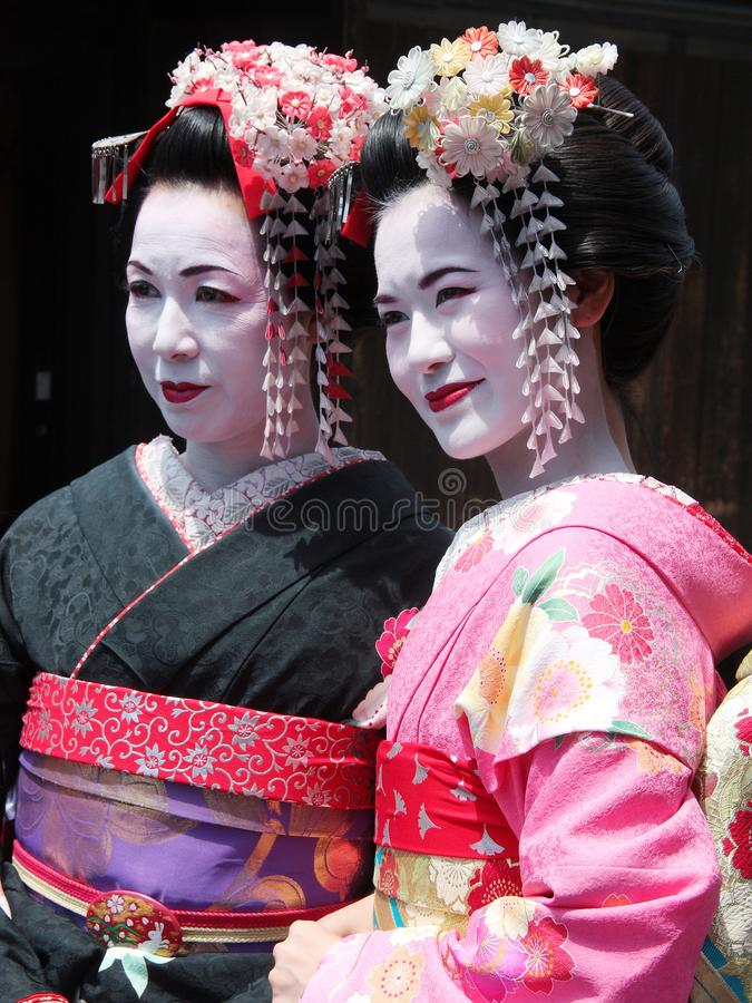 Gueixa nova e madura bonita que anda no distrito velho Japão da gueixa da cidade de Kyoto fotos de stock