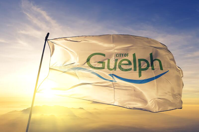 Guelph of Ontario of Canada flag waving on the top sunrise mist fog. Guelph of Ontario of Canada flag textile cloth fabric waving on the top sunrise mist fog stock image