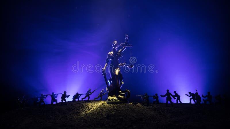 Guerra- nessun concetto della giustizia Siluette militari che combattono scena e la statua di giustizia su un fondo nebbioso toni fotografia stock