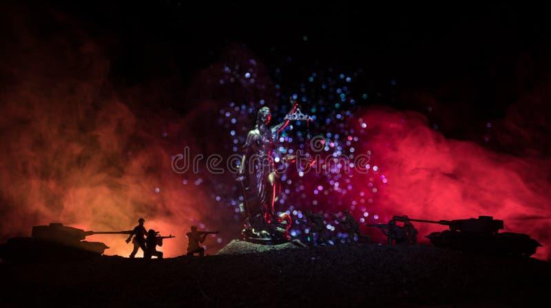 Guerra- nessun concetto della giustizia Siluette militari che combattono scena e la statua di giustizia su un fondo nebbioso toni fotografie stock