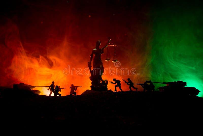 Guerra- nessun concetto della giustizia Siluette militari che combattono scena e la statua di giustizia su un fondo nebbioso toni immagine stock