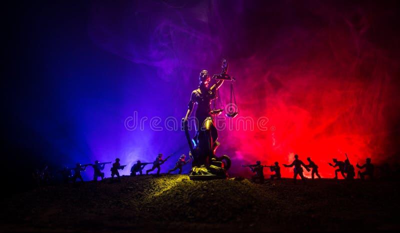 Guerra- nessun concetto della giustizia Siluette militari che combattono scena e la statua di giustizia su un fondo nebbioso toni fotografia stock libera da diritti