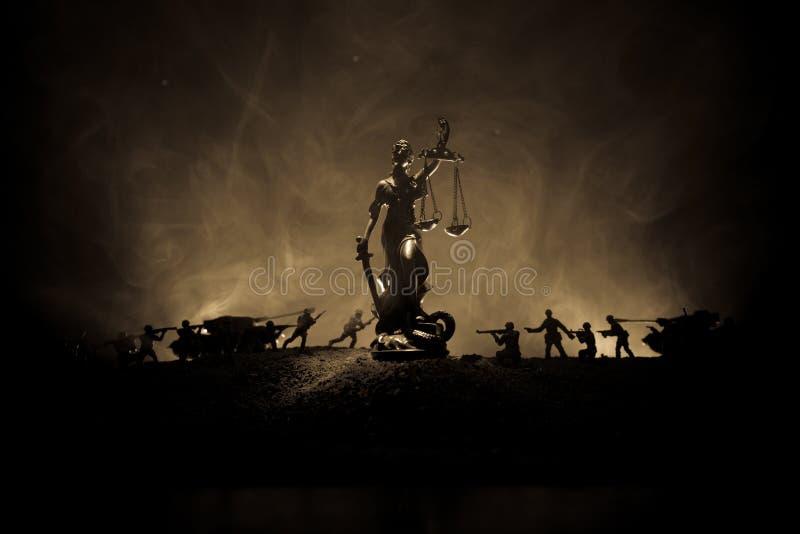 Guerra- nessun concetto della giustizia Siluette militari che combattono scena e la statua di giustizia su un fondo nebbioso toni fotografie stock libere da diritti