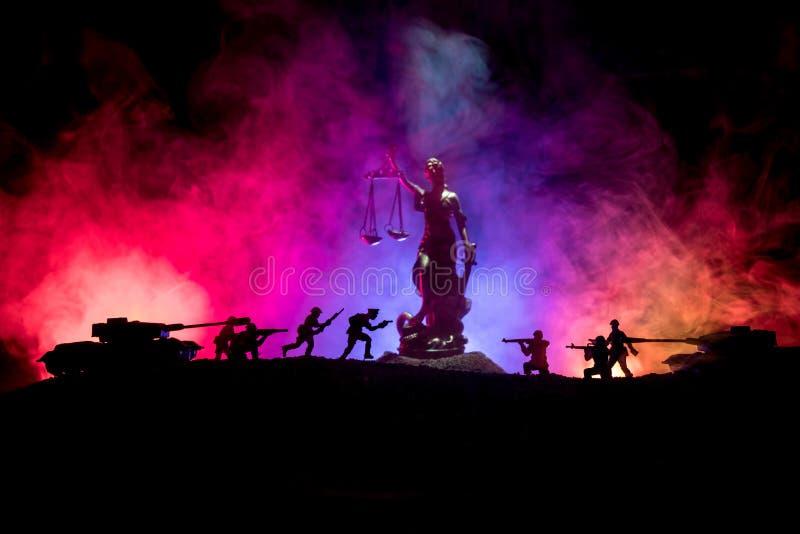 Guerra- nessun concetto della giustizia Siluette militari che combattono scena e la statua di giustizia su un fondo nebbioso toni immagini stock