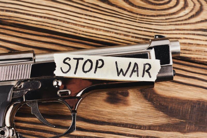 GUERRE d'ARRÊT d'inscription sur le papier déchiré et le pistolet brillant photos stock