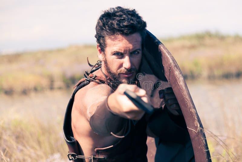 Guerreiro antigo de combate na armadura com espada e protetor imagem de stock