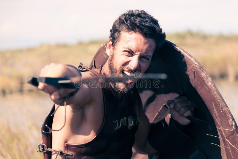 Guerreiro antigo de combate na armadura com espada e protetor fotos de stock royalty free