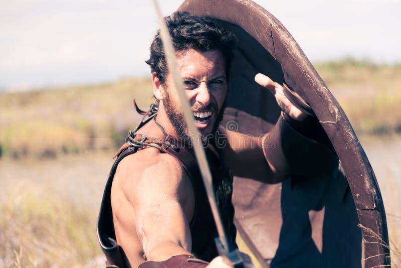 Guerreiro antigo de combate na armadura com espada e protetor fotos de stock