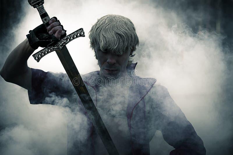 Guerreiro brutal com a espada no fumo imagens de stock royalty free