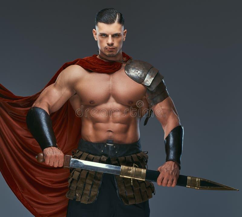 Guerreiro brutal de Grécia antigo com um corpo muscular em uniformes da batalha fotos de stock