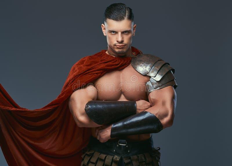 Guerreiro brutal de Grécia antigo com um corpo muscular nos uniformes da batalha que estão com braços cruzados imagens de stock