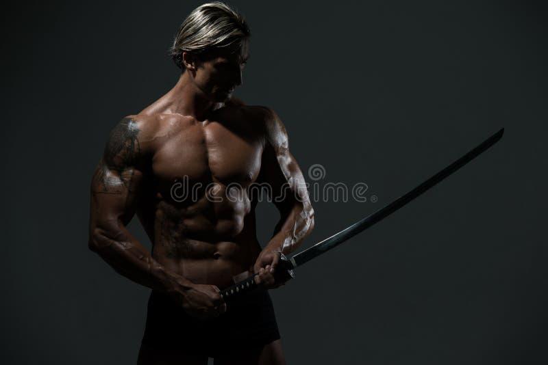 Guerreiro com a espada longa sobre o fundo preto foto de stock