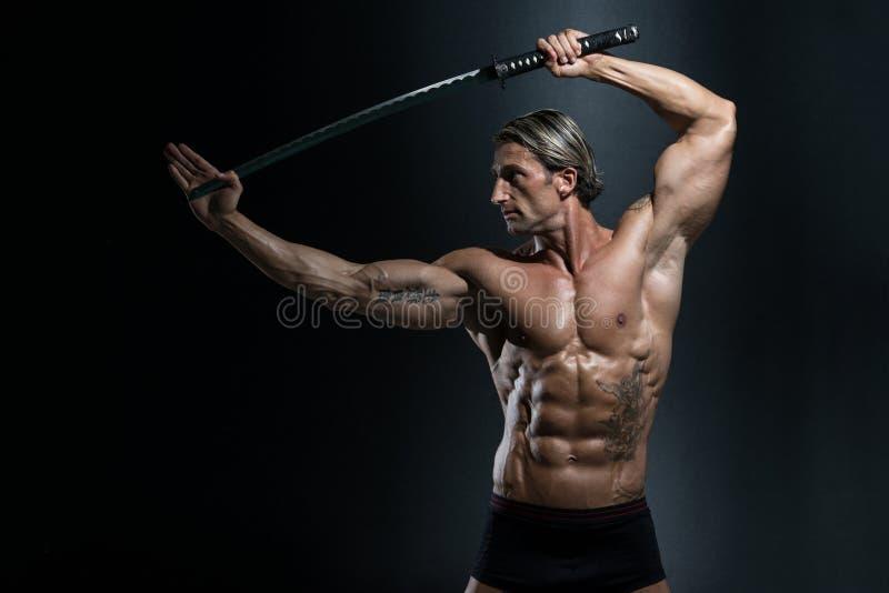 Guerreiro com a espada longa sobre o fundo preto fotos de stock royalty free