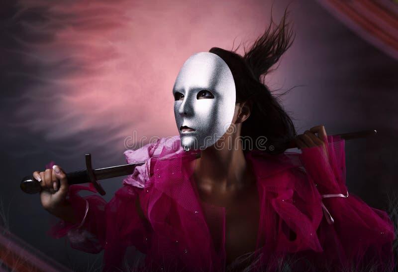 Guerreiro da mulher na máscara de prata com uma espada fotografia de stock royalty free