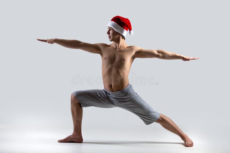 Guerreiro 2 da pose da ioga no chapéu de Santa Claus fotografia de stock