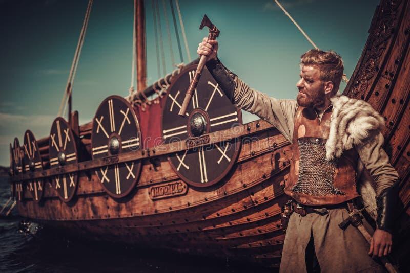 Guerreiro de Viking com os machados que estão perto de Drakkar no litoral imagens de stock royalty free