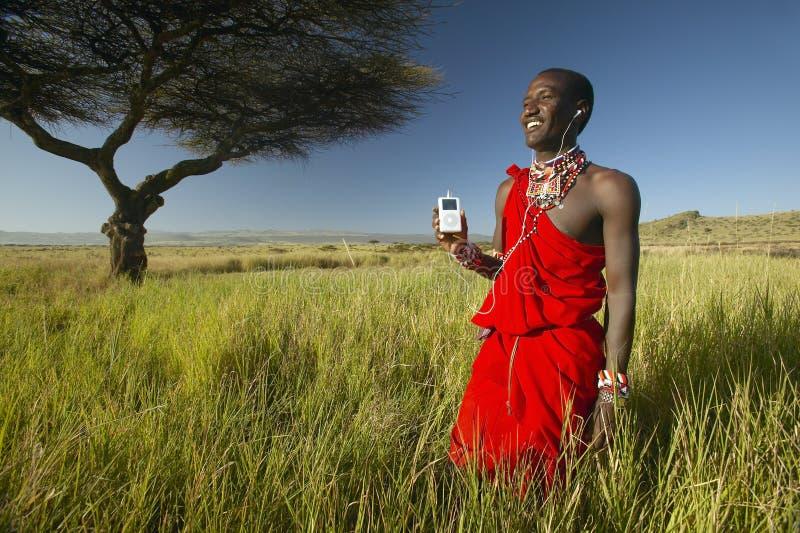 Guerreiro do Masai perto da árvore da acácia que escuta a música em iPod por Apple na paisagem de exame vermelha da tutela de Lew foto de stock royalty free