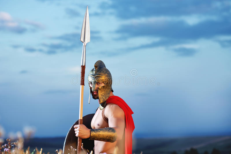 Guerreiro espartano forte no vestido de batalha com um protetor e uma lança foto de stock royalty free