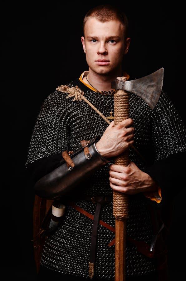 Guerreiro medieval masculino na armadura e correio chain, viquingue com bateria imagem de stock