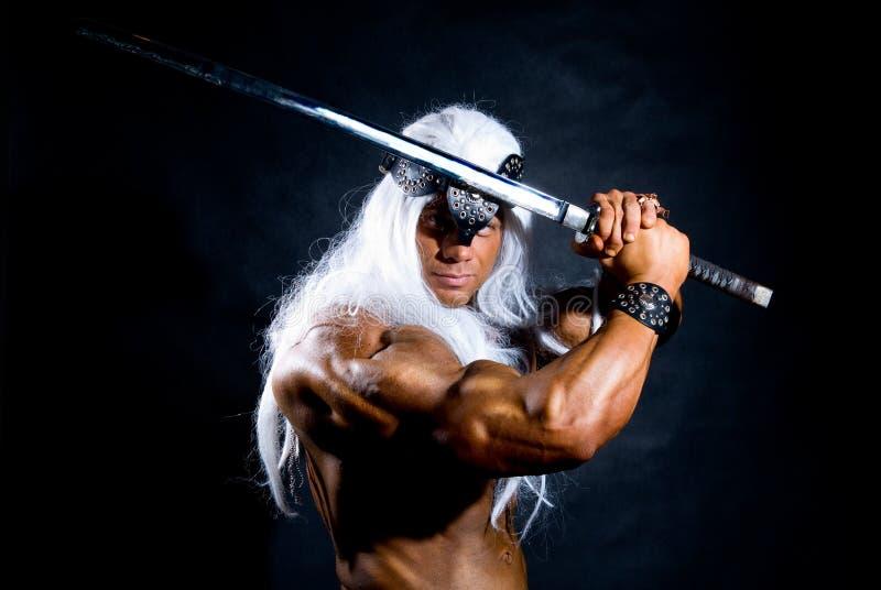 Guerreiro muscular despido do homem com uma espada. imagens de stock royalty free