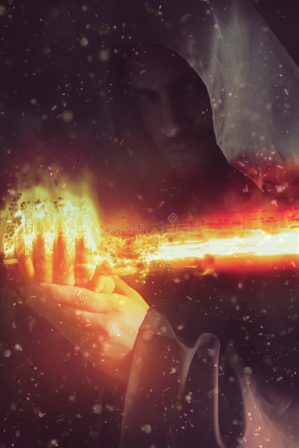 Guerreiro novo que guarda um sabre no fogo imagem de stock royalty free
