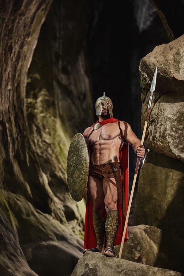 Guerreiro poderoso com a arma que levanta em rochas fotografia de stock