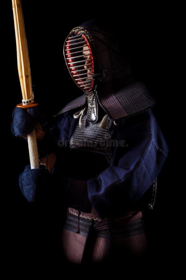Guerrero de Kendo en vestido tradicional en un fondo negro fotografía de archivo