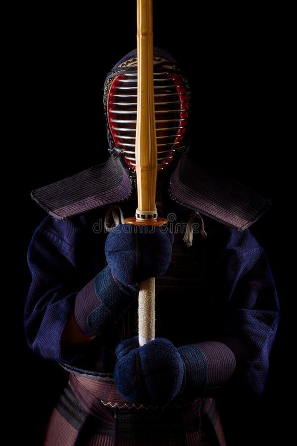 Guerrero de Kendo en vestido tradicional en un fondo negro foto de archivo libre de regalías