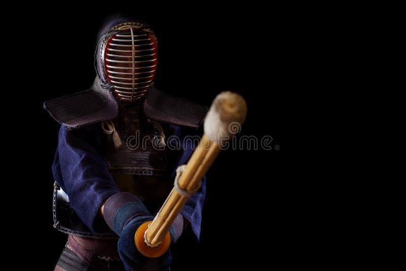 Guerrero de Kendo en vestido tradicional en un fondo negro fotos de archivo