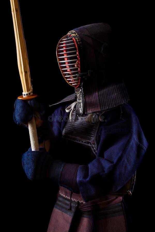 Guerrero de Kendo en vestido tradicional en un fondo negro imagen de archivo