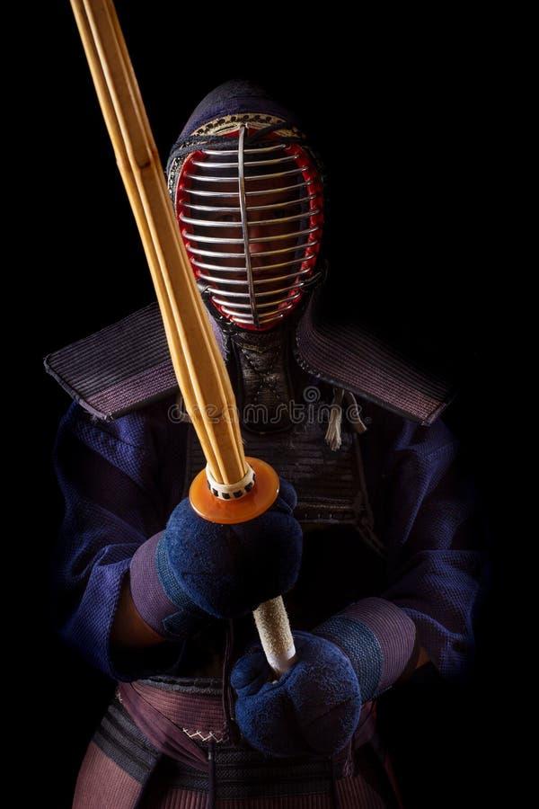 Guerrero de Kendo en vestido tradicional en un fondo negro foto de archivo